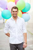 Man with colorful balloons in the city Royalty Free Stock Photography