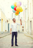 Man with colorful balloons in the city Stock Images