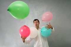 Man with colorful baloons. Confused man with colorful baloons Royalty Free Stock Photo