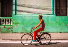 Man with colorful cloths riding a bike stock photo