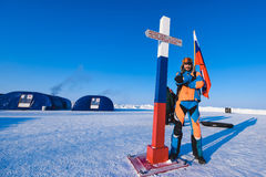 Man in a Colorful down jacket Fur cap Beard and mustache in a frost in the background of the camp Barneo on a snowy north pole in royalty free stock photography