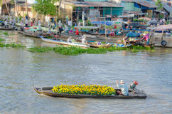 The man and colorful flowers boat at Nga Nam floating market Royalty Free Stock Photo