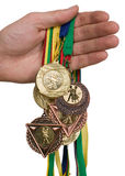 Man with colorful medals. Man is holding various medals in his hand Royalty Free Stock Photo