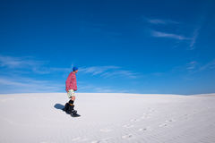 Man in colorful shirt slides down on a snowboard on the sand dun Royalty Free Stock Photography