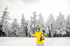 Man snowboarding at the mountains. Man in colorful sports clothes riding the snowboard on the snowy mountains with beautiful trees on the background stock image