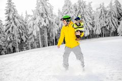 Man snowboarding at the mountains. Man in colorful sports clothes riding the snowboard on the snowy mountains with beautiful trees on the background stock photos