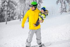 Man snowboarding at the mountains. Man in colorful sports clothes riding the snowboard on the snowy mountains with beautiful trees on the background stock images