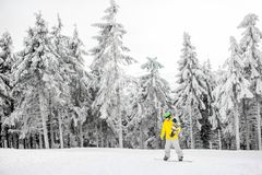 Man snowboarding at the mountains. Man in colorful sports clothes riding the snowboard on the snowy mountains with beautiful trees on the background. Wide angle stock image