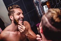 Man combing beard in the bathroom stock photo