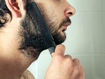 Man combing beard hair closeup Royalty Free Stock Photo