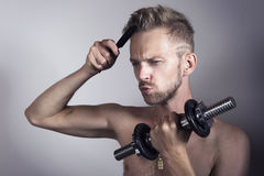Man combing hair and lifting weights. Attractive man working out and combing his hair Royalty Free Stock Photography