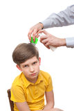 Man combs out nits at the young boy. And sprinkles hair by medical spray stock image