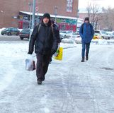 man comes from  grocery store in  winter jacket  frosty day. Russia, Moscow, February 2018 man comes from  grocery store in winter jacket  frosty day editorial Royalty Free Stock Image