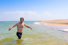 Man comes out of the sea to the beach. A in crimean. Azov sea stock photography