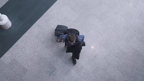 Man comes with a suitcase top view stock video footage