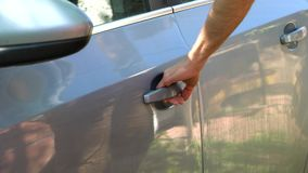 A man comes to the car, pulls the door handle several times. But the door is closed stock footage