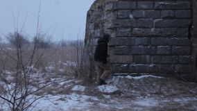 Man comes to the old house on the street where it snows and winter stock footage