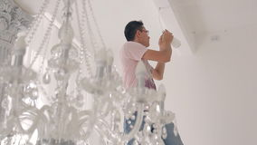 Man comes up on stairs to screw lamps in chandelier in big house stock footage
