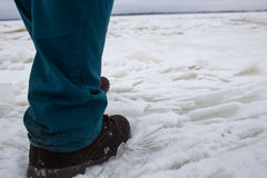 Man Comes On The Weak Bad River Ice. Concept danger falling through the ice Stock Photo