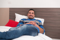 Man Comfortably REsting In His Bed Stock Photo