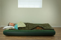 Man comfortably sleeping on blow up air mattress bed in sleeping bag. With clean walls and window in the background Stock Photo