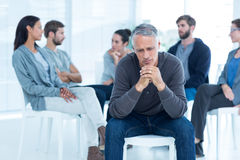 Man comforting another in rehab group at therapy. Man comforting another in rehab group at a therapy session Stock Image