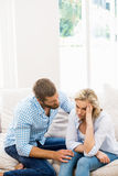 Man comforting her woman in living room Stock Photo