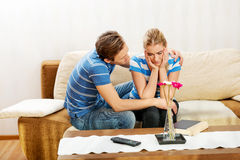 Man comforting his upset partner in living room Stock Photo