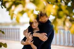 Man comforting his woman outdoor. Man in love comforting his smiling women outdoor Stock Image