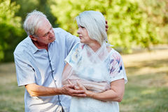 Man comforting old woman with broken arm Stock Photo