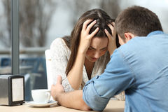 Man comforting a sad depressed girl. Male comforting to a sad depressed female who needs help in a coffee shop. Break up or best friend concept Stock Images