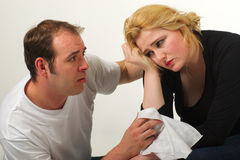 Man comforting woman. Man in white t-shirt is comforting a blond women kneeling beside her and holding a white handkerchief Royalty Free Stock Photo