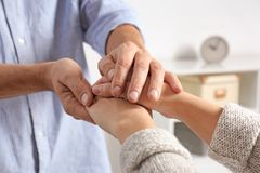 Man comforting woman on blurred background, closeup of hands. royalty free stock images