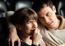 Man Comforting Woman Crying While Watching Movie. Mid adult men comforting women crying while watching movie in cinema theater stock photo