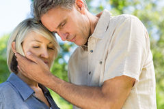 Man comforting woman in park Royalty Free Stock Image