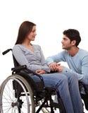 Man comforting woman in wheelchair. Man comforting a young woman in a wheelchair Royalty Free Stock Photos