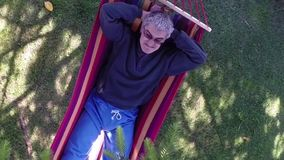 Man With Comical Expression Relaxing In Hammock. Caucasian middle-aged man with comical expression relaxing in hammock, aerial view stock video