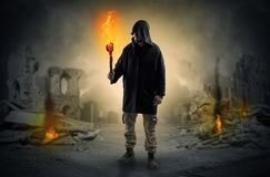 Man coming with burning flambeau at a catastrophe scene concept. Destroyed place after a catastrophe with man and  burning flambeau conceptn Royalty Free Stock Image