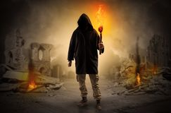 Man coming with burning flambeau at a catastrophe scene concept. Destroyed place after a catastrophe with man and  burning flambeau conceptn Stock Photo