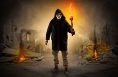 Man coming with burning flambeau at a catastrophe scene concept. Destroyed place after a catastrophe with man and  burning flambeau concept royalty free stock photography