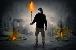 Man coming with burning flambeau at a catastrophe scene concept. Destroyed place after a catastrophe with man and  burning flambeau concept royalty free stock image