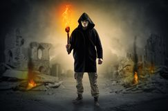 Man coming with burning flambeau at a catastrophe scene concept. Destroyed place after a catastrophe with man and  burning flambeau conceptn royalty free stock photo
