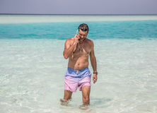 Man is coming out of the deep blue water of Indian ocean and speaking y telephone Royalty Free Stock Images