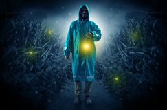 Man coming out from a thicket with lantern. Man in raincoat at night coming from thicket and looking something with glowing lanternn Royalty Free Stock Images