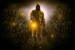 Man coming out from a thicket with lantern. Man in raincoat at night coming from thicket and looking something with glowing lanternn Royalty Free Stock Photo