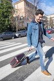 Tourist arrived in town with a small trolley. Man coming to town with a small luggage Stock Photo