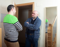 Man coming to visit his friend. Adult men meeting another men at door royalty free stock photo