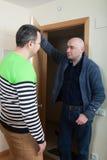 Man coming to visit his friend. Adult men opening door his neighbor stock photography