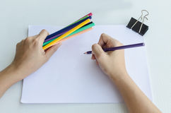 Man commencing sketching in a sketch book. Man holding a fistful of colored pencils in one hand while commencing sketching in a sketch book to show off his Royalty Free Stock Photos