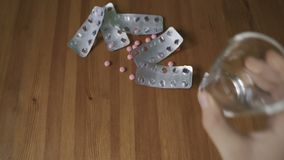 A man commits suicide. Takes a lethal dose of pills. A man holds in his hand and takes a large dose of pink pills and washes down with water. Man commits suicide stock video footage